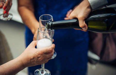 Man fills glasses of champagne for guests at festive dinner. Hand holding a bottle, close-up. Pouring drinks to friends and relatives at wedding banquet. 免版税图像