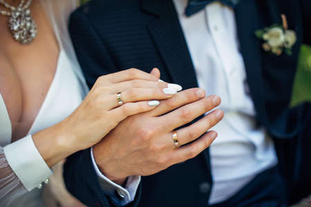 Hands of the bride and groom close-up, blurred background. Gold wedding rings on the fingers of newlyweds. Concept of marriage.