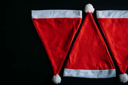 Red Father Christmas hats isolated on black background, top view, close up. Santa's hat with space for text. New year concept. 免版税图像