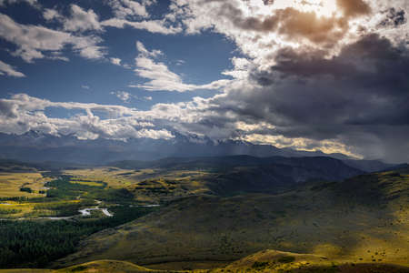 Majestic panorama of mountain plain on the background of snow-covered ridge before thunderstorm. Sun's rays break through huge clouds and beautifully illuminate green steppe and winding river. 免版税图像