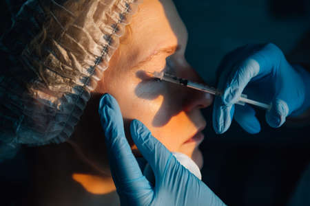 Female patient getting hyaluronic acid injection, dark background, close up. Acne treatment on woman face, plasma-lifting, mesotherapy, botulinum therapy. PRP Cosmetics Injecting. Anti-aging concept.