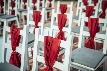 White wooden chairs decorated with red fabric and ribbons for wedding registration outdoor. Guest chairs in rows, close up.
