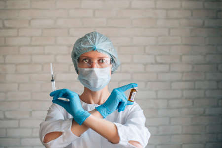 Scientist woman wearing protective suit and mask holds in crossed hands syringe and ampule. Female doctor in hospital ready for procedure. Clinical trials of new coronavirus covid 19 vaccine.