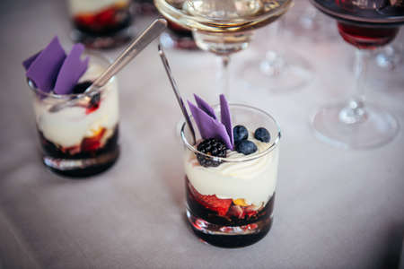 Delicious dessert of whipped cream and fresh berries in glass with spoon. Portioned sweet snacks in restaurant at festive banquet. Blackberries, blueberries, strawberries, berry topping, butter cream.