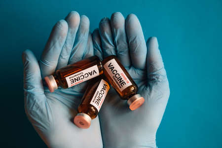 Hands in latex gloves holding vials of new coronavirus vaccine, close up on blue background. Medics and scientists against covid-19 pandemic. Medicine ready to test on volunteers.