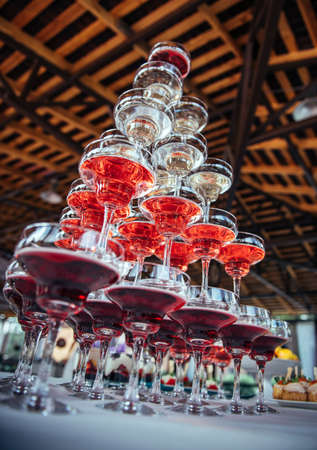 High pyramid of wine glasses filled with white and red champagne, view from below. Welcome drink. Organization of an off-site banquet, catering.