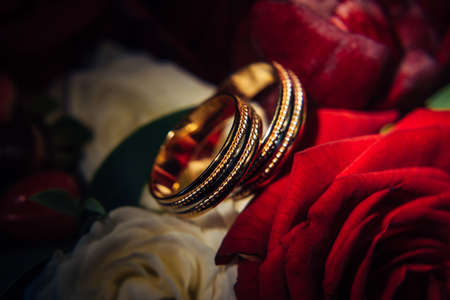 Gold wedding rings on background of red flowers, selective focus, close-up. Vintage rings, reflections of light, rosebuds, macro photography.