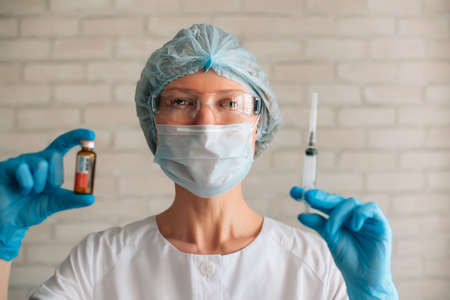 Scientist woman wearing protective suit and mask holding syringe and vial. Female doctor in hospital ready for procedure. Clinical trials of new coronavirus covid 19 vaccine. 版權商用圖片