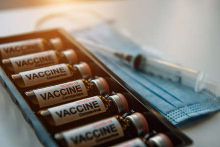 Close-up of glass vials with Covid-19 vaccine, medical mask, syringe. Scientific developments in the fight against viral infection, coronavirus, pulmonary pneumonia.