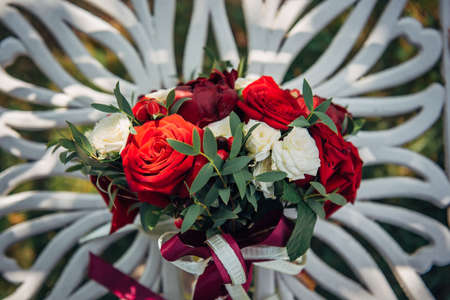 Bright flower arrangement of red and white roses on light blurry background, close-up. Wedding bouquet of fresh flowers with green twigs and satin ribbons.