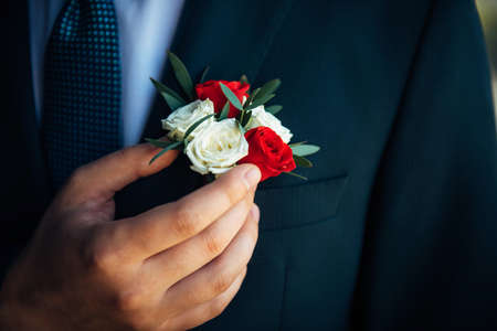 Boutonniere of white and red roses in the buttonhole of a classic jacket. Groom touches boutonniere, man's hand close-up. Wedding concept, accessories for newlyweds.