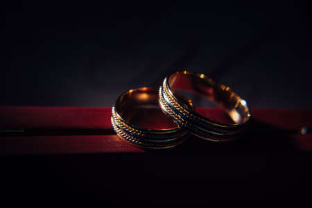 Two vintage wedding rings on dark red background, close-up. Gold rings with a pattern, selective focus. Jewelry for the bride and groom. 版權商用圖片