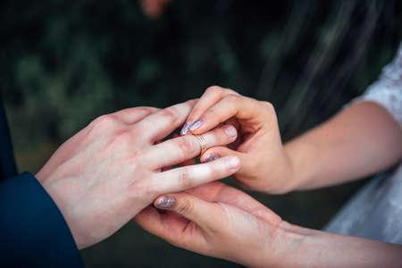Bride putting gold wedding ring on groom's finger during wedding ceremony, close up, blurred background. 版權商用圖片