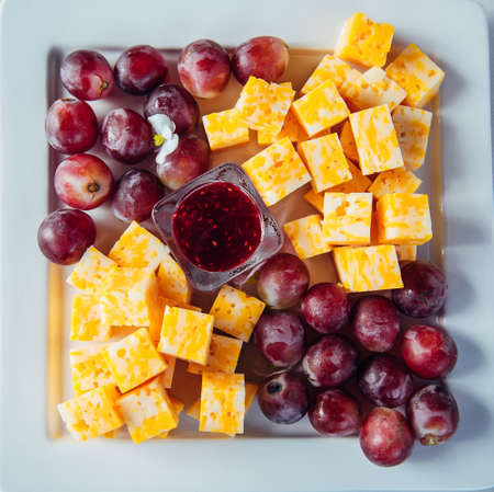 Delicious gourmet appetizer of marble cheese, red grapes and raspberry jam on white plate, close-up. Cold snacks in the restaurant. Catering.