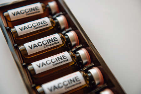Bottles of vaccine to fight the coronavirus pandemic. Sars-cov-2 / COVID-19. Some ampoules with vaccine in a box on white background, close up.