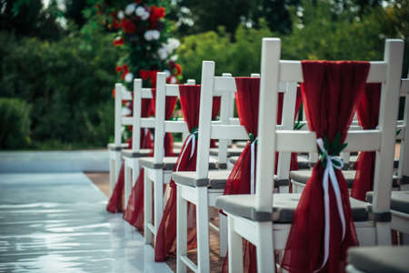 White wooden chairs decorated with red fabric and ribbons for wedding reception outdoor. Guest chairs in rows in the summer park, blurred background.