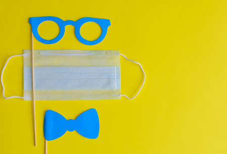 Medical face mask and paper glasses on stick on bright yellow background, close-up. April Fools' Day and coronavirus pandemic. Accessories for jokes and parties.