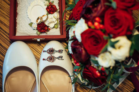 Vintage wedding jewelry and accessories, close-up. Gold wedding rings, ruby earrings, classic bride's shoes, bouquet of fresh red and white roses.