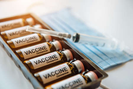 Coronavirus COVID-19 vaccine ampoules in a box, blurred background, close up. Vials with drug, label, syringe, medical mask, selective focus.