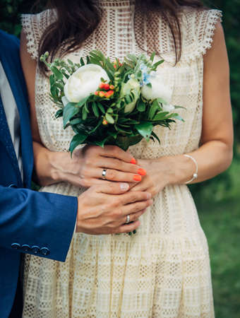Hands of the bride and groom with wedding rings, bouquet of fresh flowers, vintage lace dress. Concept of marriage, love, family life.