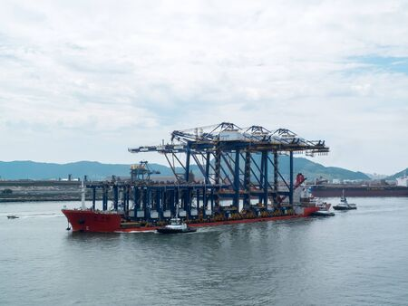 Santos, Brazil, 16, February 2013: A heavy lift vessel loaded with shore gantry cranes on a river passage, entering port of Santos.