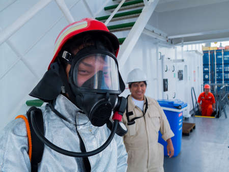International waters, 10, February 2013: An asian seafarer wearing fire fighter suit and breathing apparatus during fire drill on board.