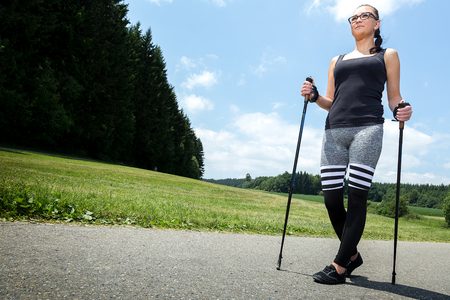 Young woman doing exercises at Nordic walking Stock Photo