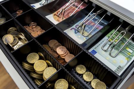 Registratore di cassa con monete e carta moneta
