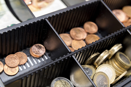 Cash register with coins and paper money