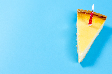 Cheese cake with a candle on blue background Stock Photo