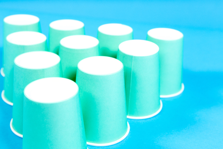 Green paper cups on blue background Stock Photo