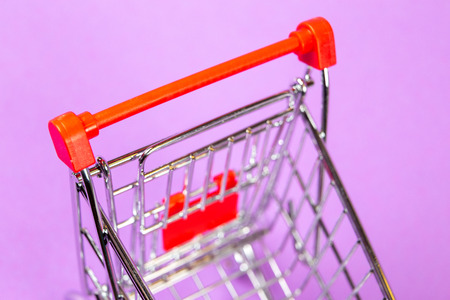 Empty shopping cart on the lilas background Foto de archivo - 99360192