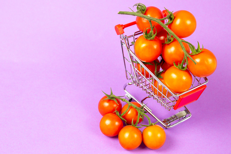Shopping cart full with tomatoes on purple background