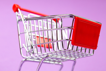 Empty shopping cart on the lilas background Foto de archivo - 99364475