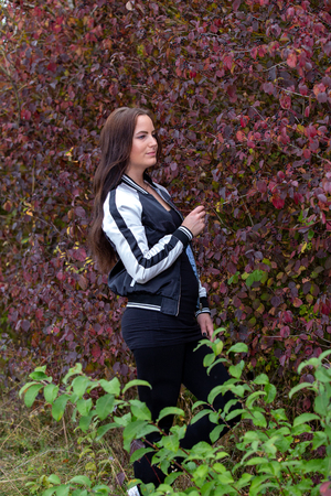 Brunette in a tracksuit posing near the bushes, germany