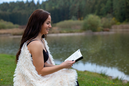 Brunette near the lake is reading a book,germany