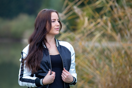 Brunette in tracksuit posing by the lake, germany