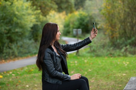 Brunette in a black leather jacket on a bench takes a selfie, germany