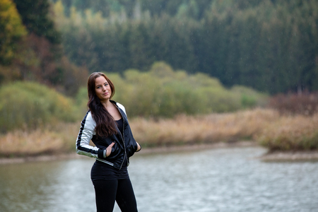 Brunette in tracksuit posing by the lake,germany Standard-Bild