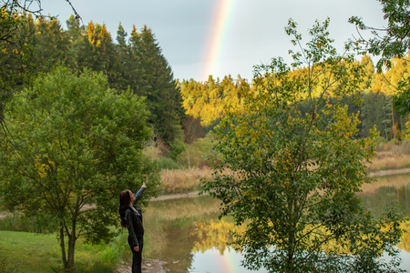 Brunette in a black leather jacket near the lake admires a rainbow, germany Standard-Bild