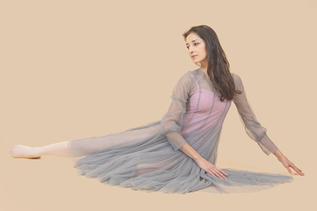 Ballerina dance in a gray dress on a beige background