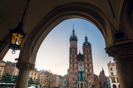 Beautiful view of Saint Marys Basilica from Cloth Hall building Sukiennice. Main market square in Krakow, Poland. Passage of the gothic hall with columns.