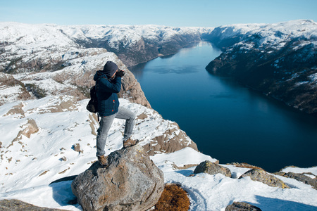 Traveller man taking photo of the fjord and rocky mountains on the camera while standing on the top of the Pulpit Rock, Preikestolen Norwegian mountains. Lysefjord, Norway