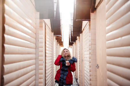 Happy beautiful blonde girl with curly hair in red winter jacket with hot coffee walking between wooden booths on Christmas fair Stock Photo