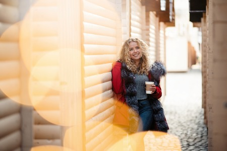 Portrait of happy beautiful blonde girl with curly hair in red winter jacket with hot coffee standing near the wooden bkiosk on Christmas fair Stock Photo