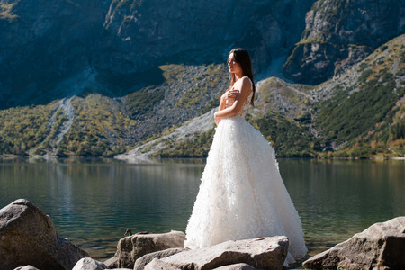 Beautiful bride in gorgeous white wedding dress standing near the lake Morskie Oko in the mountains on sunny summer day Фото со стока