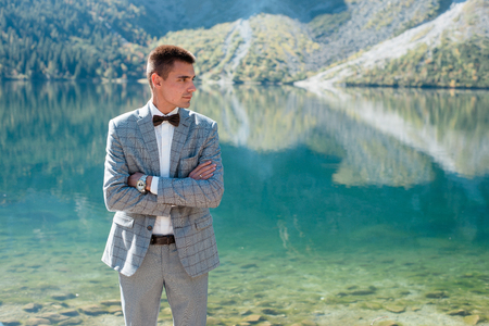Handsome groom in wedding suit standing near the lake in the mountains. Morskie Oko Фото со стока