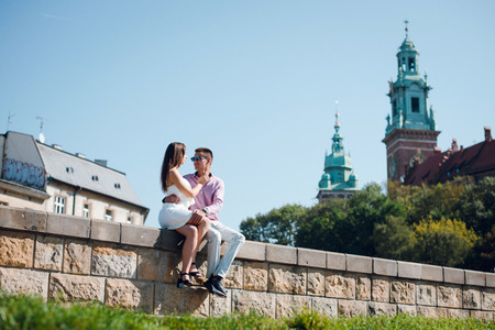 Romantic young couple sitting on the street near the Wavel castle in Krakow, Poland