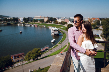Beautiful young couple standing near the lake Wisla in Krakow, Poland. Sunny summer day Stock fotó