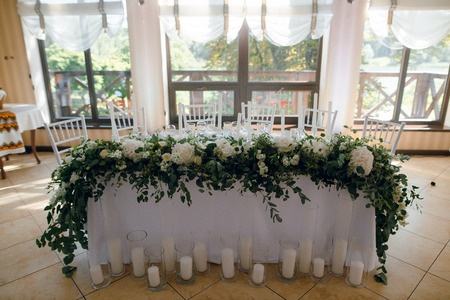 Wedding table decoration with the white flowers and greenery for the fiance and fiancee at the restaurant